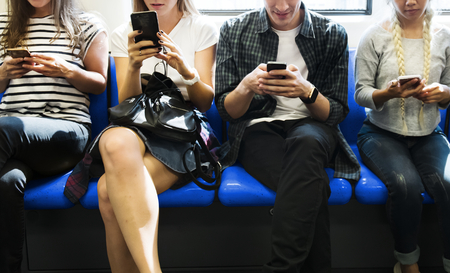 Group of young adult friends using smartphones in the subway Archivio Fotografico