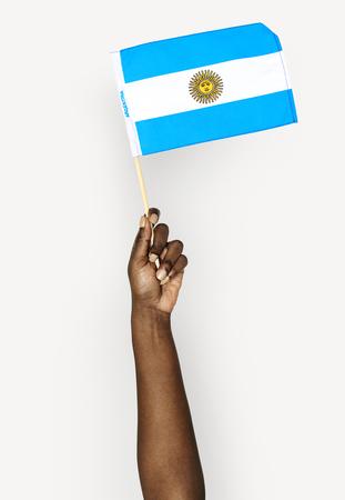 Hand holding an Argentina flag