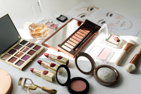 Various makeup products on white table Archivio Fotografico
