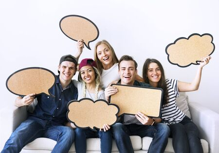Happy young adults holding up copyspace placard thought bubbles Stockfoto