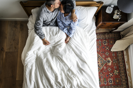 Cute interracial couple on the bed kissing Stock Photo