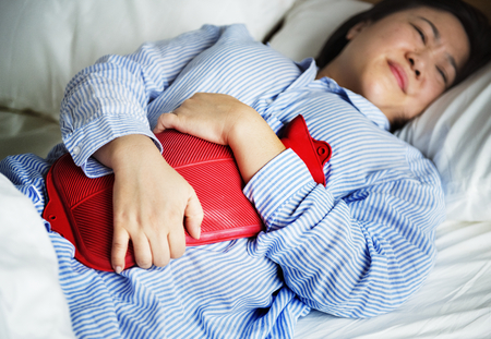 A woman in pain holding a hot water bottle