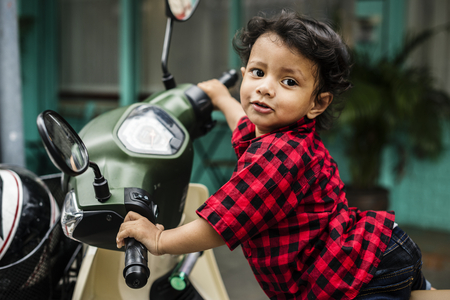 Young Indian boy riding the motorbike Stock Photo