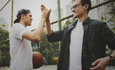 Young adult male friends playing basketball in the park