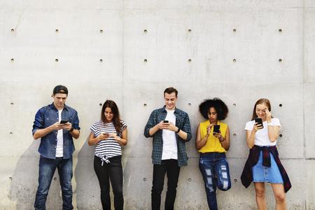 Gruppo di giovani adulti all'aperto utilizzando gli smartphone insieme e rilassarsi