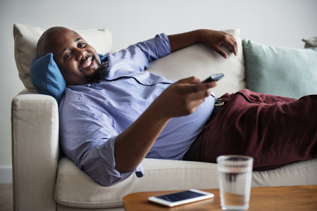 Man lying on the couch after work Stock Photo
