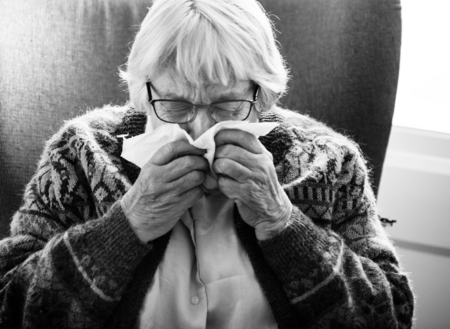Black and white photo of senior woman sneezing Stock Photo