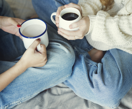 Women couple with hot drinks in winter Stock Photo