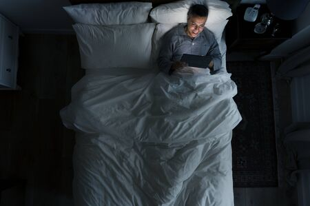 Man on bed using his tablet Stock Photo