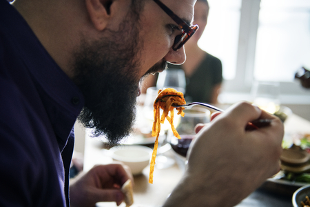 Bearded man eating pasta concept