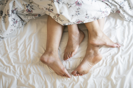 Aerial view of legs on bed