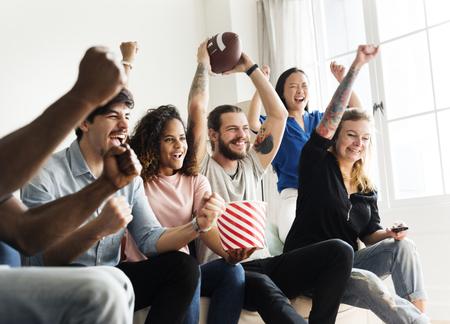 Aficionados al fútbol americano viendo el torneo en casa Foto de archivo