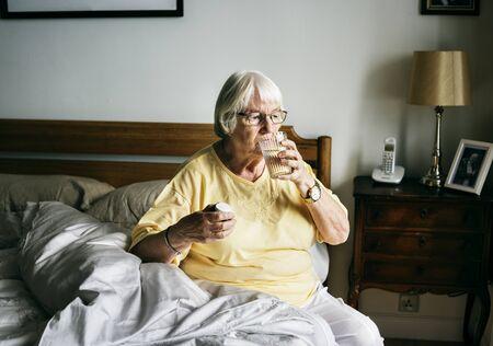 Ltere Frau , die Pillen auf ihrem Bett hat Standard-Bild - 96572864