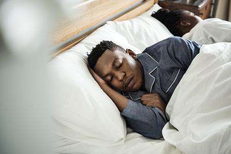 ベッドでぐっすり眠っている男 写真素材