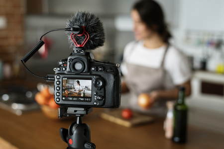 Female vlogger recording cooking related broadcast at home 스톡 콘텐츠