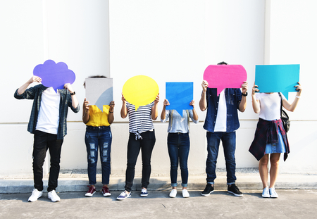 Young adult friends holding up copyspace placard thought bubbles 写真素材 - 96683983