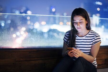 Young woman using a smartphone in the evening cityscape