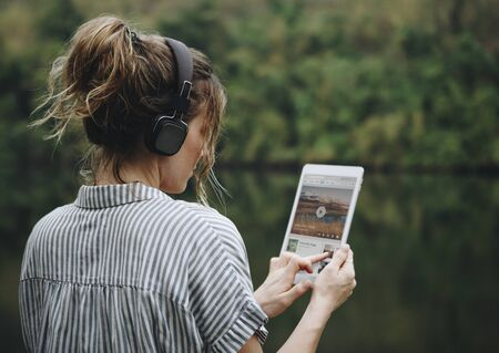 Woman alone in nature listening to music with headphones Stock Photo