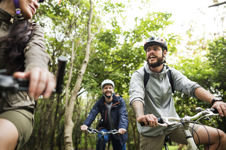 Group of friends ride mountain bike in the forest together Фото со стока