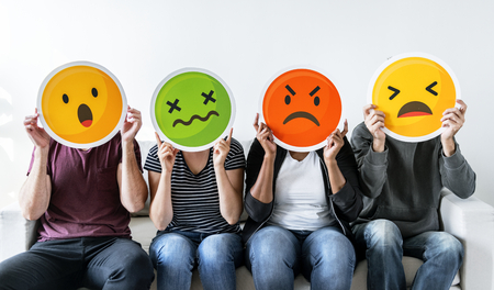Diverse people holding emoticon Stockfoto