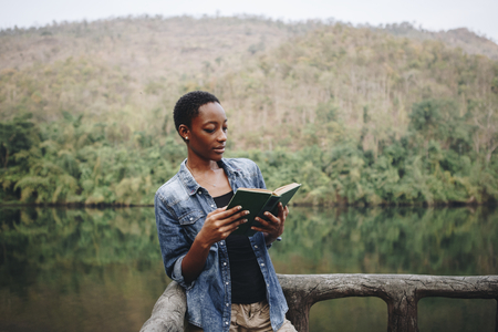 African American woman alone in nature reading a book leisure concept Stok Fotoğraf