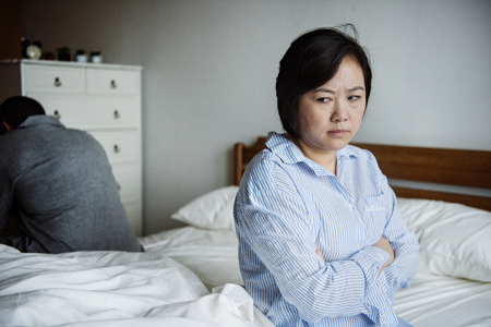 An upset woman in a bed room