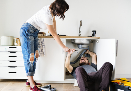 Couple fixing kitchen sink