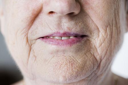 Portrait of white elderly woman closeup on smiling lips