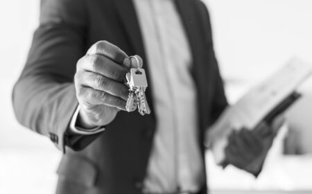 Real estate agent handing the house key Stock Photo
