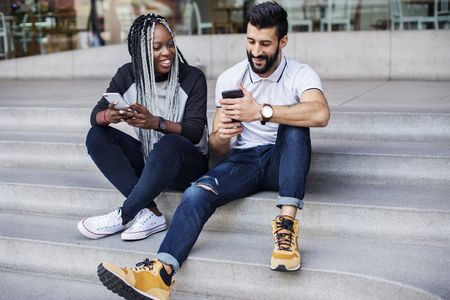 People sitting using smartphone together