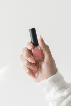 Closeup of hand holding nail polish bottle