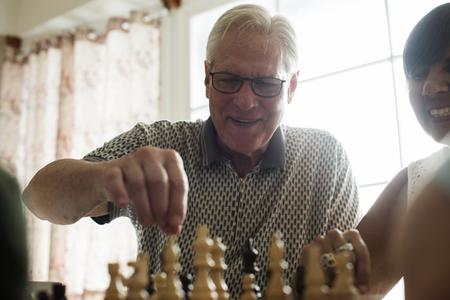 Amici senior che giocano insieme scacchi Archivio Fotografico