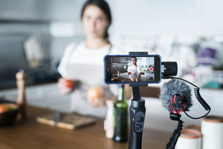Female vlogger recording cooking related broadcast at home Standard-Bild