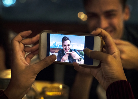 Young adult couple on a dinner date taking smartphone photos Stock Photo