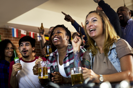 Frieds cheering sport at bar together Foto de archivo