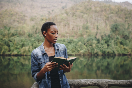 African American woman alone in nature reading a book leisure concept Stock Photo