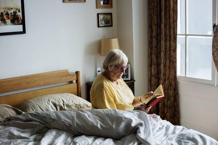 Senior woman reading on a bed Standard-Bild - 97154041