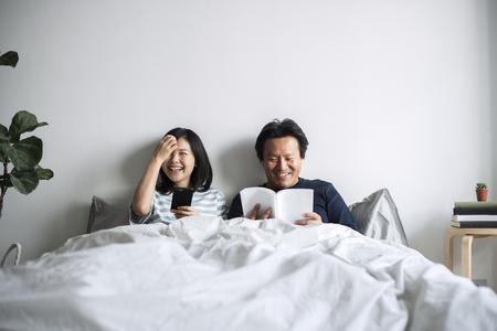 Aziatische paar ontspannen op bed samen