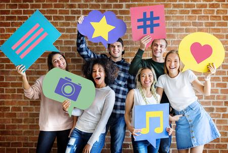 jeunes adultes heureux tenant bulle avec concept de médias sociaux icônes Banque d'images