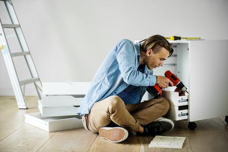 Man using electronic drill install cabinet Reklamní fotografie