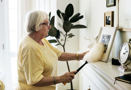 Senior woman dusting a family photo Standard-Bild - 97736568