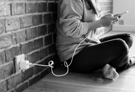 Young woman using a smartphone as it is being charged Stock fotó - 97736518