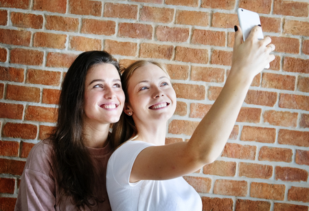 Smiling female friends taking a selfie