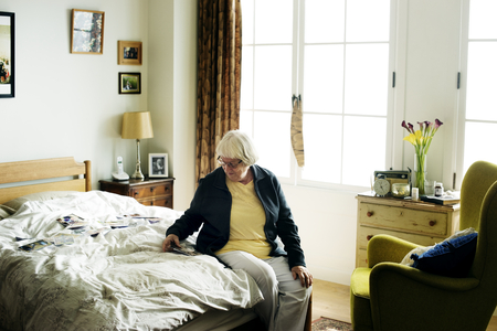 Old woman with photographs on her bed