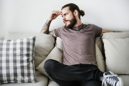 Man with tattoo sitting on a couch 스톡 콘텐츠