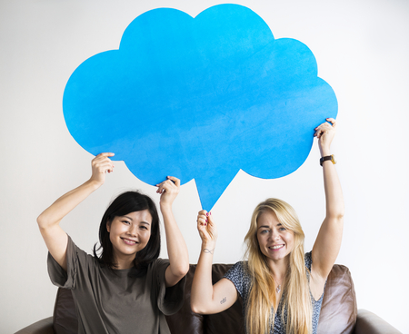 Happy Asian and Caucasian women friends holding copyspace speech bubble Banque d'images