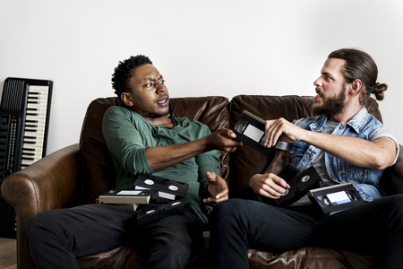 African American male and a Caucasian male hipsters fighting over VHS video tape Reklamní fotografie