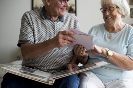 Senior couple looking at family photo album Banco de Imagens