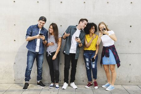 Group of young adults outdoors using smartphones together and chilling