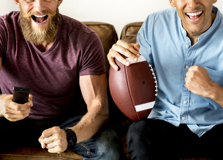 Friends cheering a game on television together 版權商用圖片